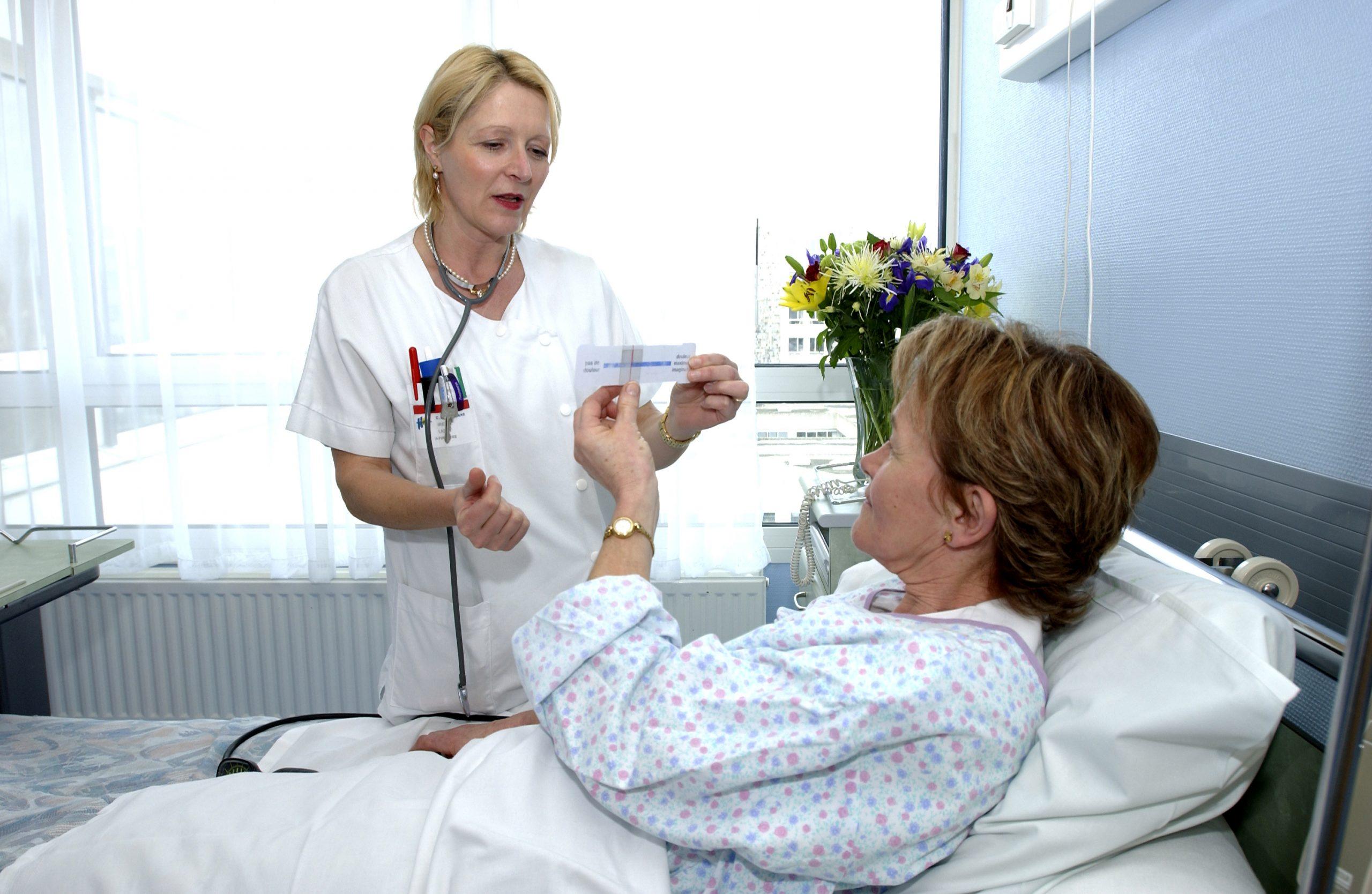 Une infirmière présente à une patiente une règle d'évaluation de la douleur.